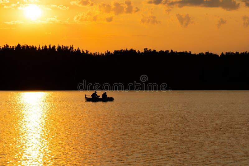 I pescatori pescano il pesce sul lago al tramonto fotografia stock libera da diritti