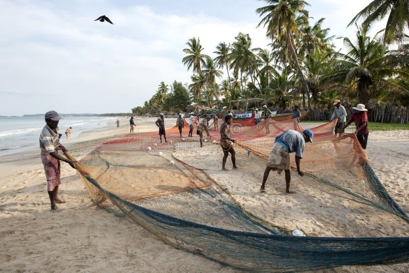 I pescatori spargono fuori le loro reti sulla spiaggia di Uppuveli nello Sri Lanka dopo che le giornate campali funzionano fotografie stock libere da diritti