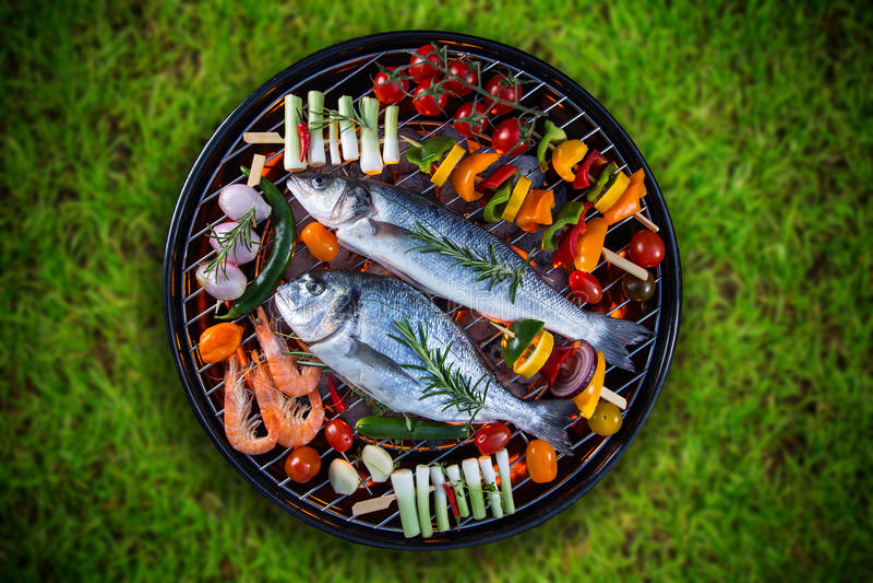 I pesci di mare arrostiti con la verdura, gli spiedi ed i gamberetti su un barbecue grigliano immagine stock libera da diritti