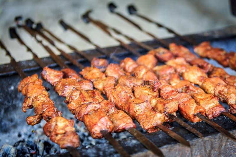 I pezzi appetitosi di carne suina sono messi insieme sugli spiedi e stanno friggendo su una griglia fotografia stock
