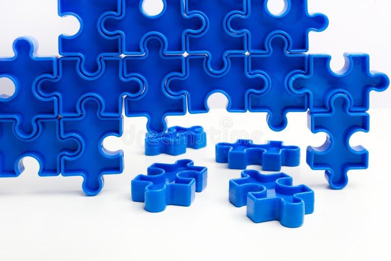 I pezzi da un puzzle blu hanno sistemato formare una pagina su fondo bianco Barriere della rottura insieme per il concetto di aut fotografia stock