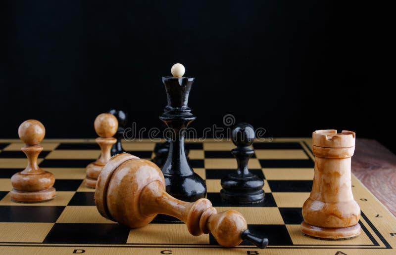 I pezzi degli scacchi sono disposti sulla scacchiera Re bianco sconfigguto immagini stock