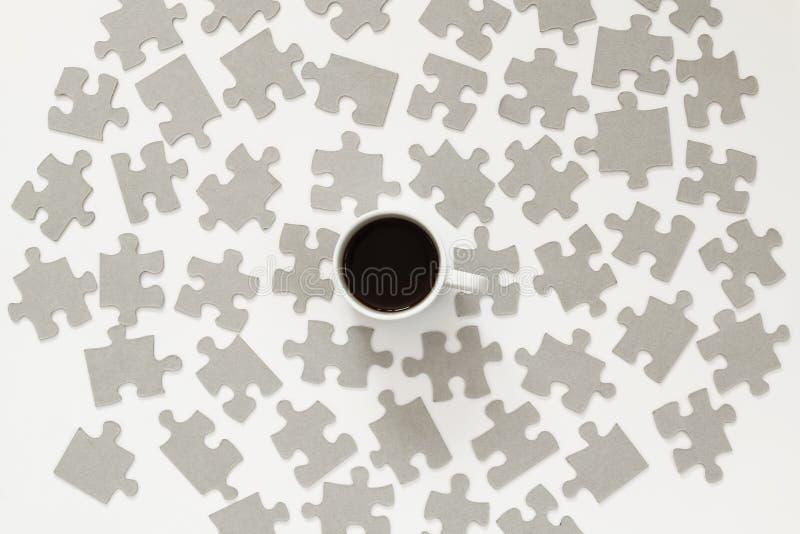 i pezzi della tazza e di puzzle di caffè hanno sparso sopra fondo bianco immagine stock