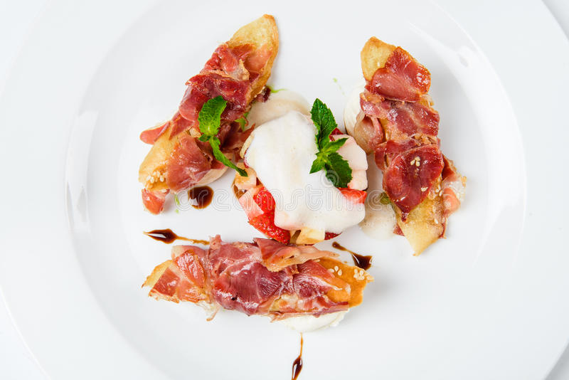 I pezzi delle baguette coperti di bacon arrostito sul piatto hanno servito il lusso immagine stock libera da diritti