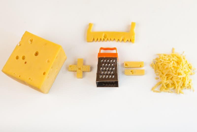 I pezzi di formaggio enorme delle forme differenti ed il metallo minuscolo grattano per la preparazione dei chees grattati immagini stock