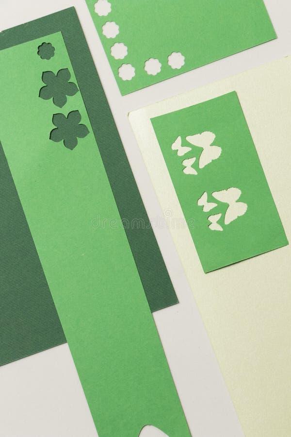 I pezzi di Libri Verde con i tipi del fiore hanno perforato le figure e le carte rimanenti delle carte perforate fotografia stock libera da diritti