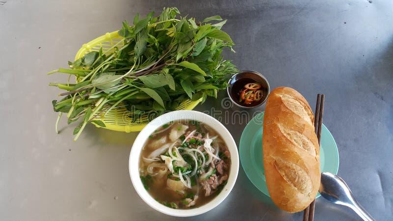 I piatti vietnamiti tradizionali includono Pho con pane e la salsa degli ortaggi freschi, del peperoncino rosso e di soia fotografia stock libera da diritti