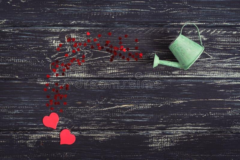 I piccoli cuori rossi versano da un annaffiatoio verde su un fondo di legno nero fotografia stock libera da diritti