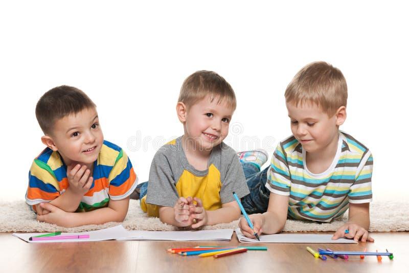 I piccoli ragazzi allegri attingono la carta fotografie stock