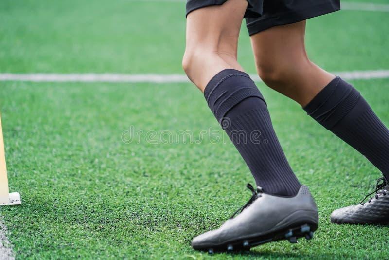 I piedi bambini si allenano correndo e si muovono nel campo dell'accademia di calcio Youth Footballer si occupa di attrezzature i immagini stock