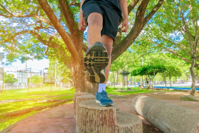 I piedi correnti di vista maschio da sotto nell'esercizio pareggiante del corridore con le vecchie scarpe in parco pubblico per s fotografia stock libera da diritti