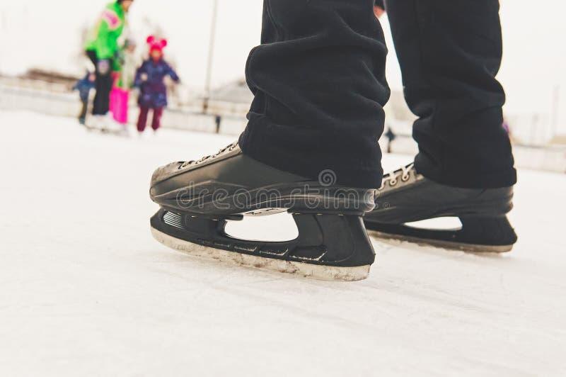 I piedi degli uomini nella pista di pattinaggio di pattinaggio su ghiaccio in pattini neri sui precedenti della gente divertente  immagini stock libere da diritti