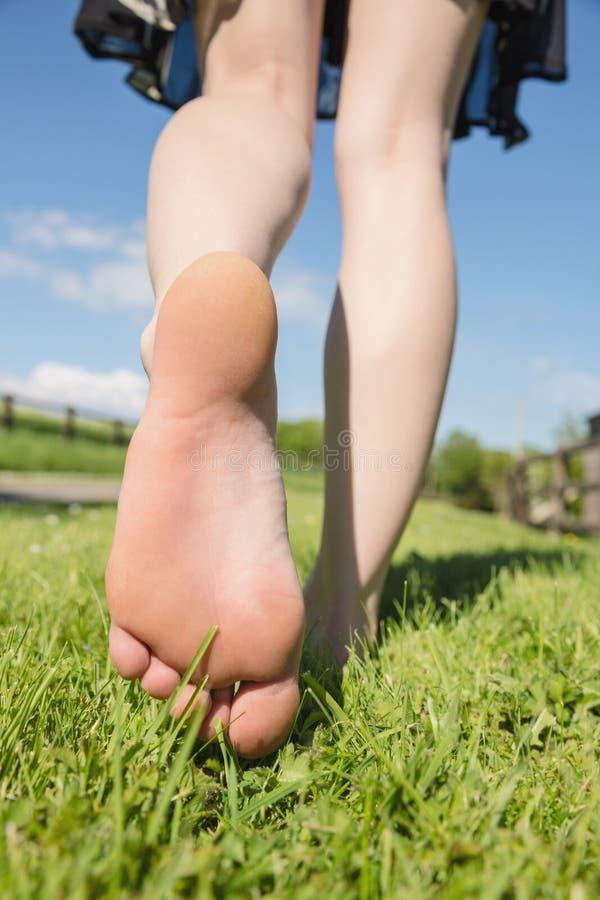 I piedi della donna che si allontanano sull'erba immagini stock libere da diritti