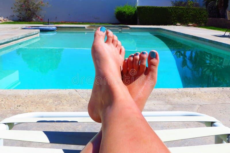 I piedi di una donna che si rilassano dallo stagno fotografia stock