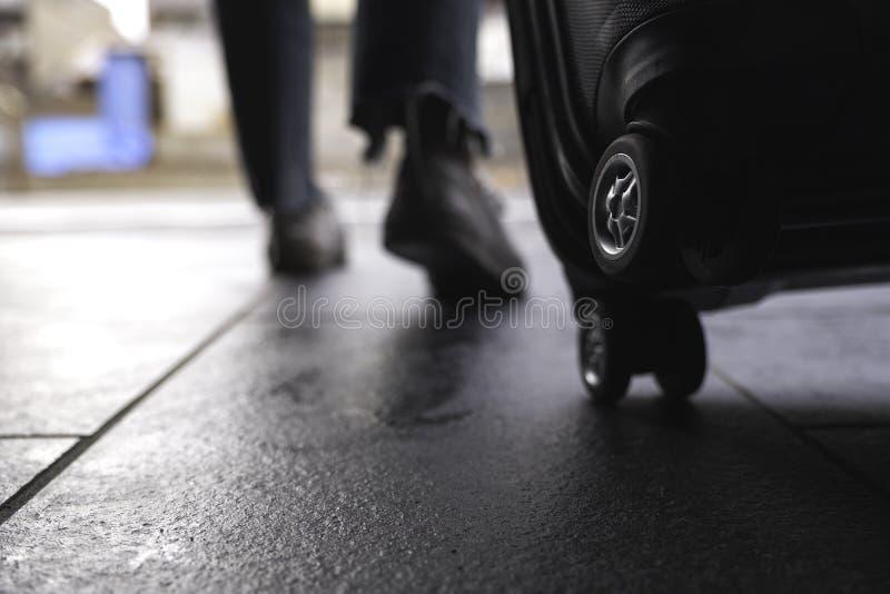 I piedi di una donna mentre viaggiando e trascinando un bagaglio nero nell'aria aperta immagini stock libere da diritti