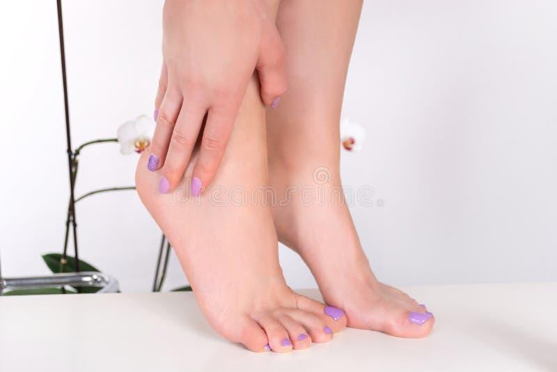 I piedi e le mani femminili con le unghie lilla lucidano il colore fotografia stock libera da diritti