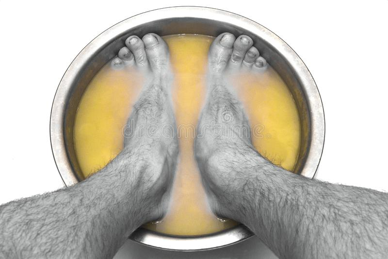 I piedi maschii in un bacino con senape sale le sue gambe, su uno sfondo naturale bianco fotografia stock