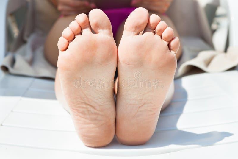 I piedi nudi della donna che si abbronzano alla località di soggiorno immagine stock libera da diritti