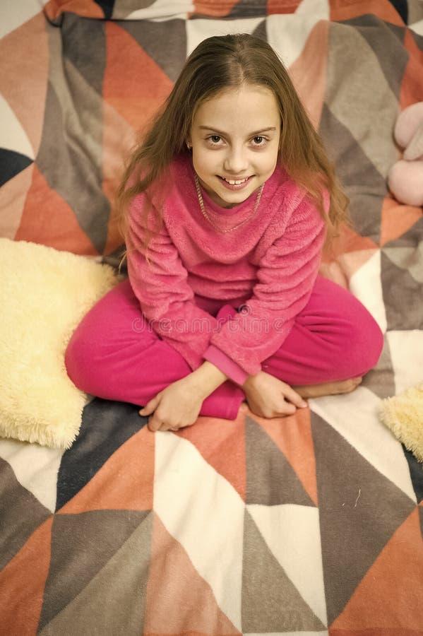 I pigiami comodi per si rilassano Il bambino della ragazza porta i pigiami svegli molli mentre si rilassa sul letto Rilassamento  immagine stock libera da diritti