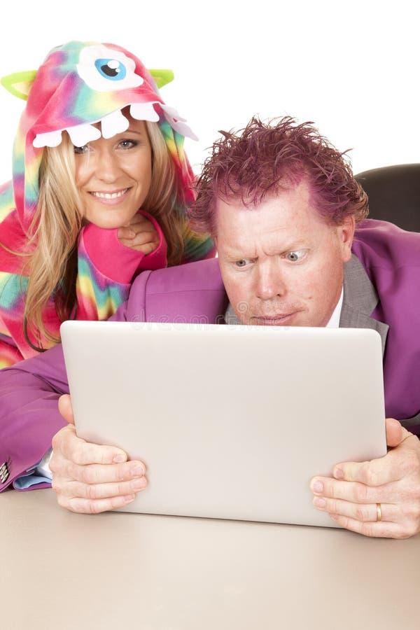 I pigiami porpora della donna del computer del vestito dell'uomo sopra la spalla sorridono fotografie stock