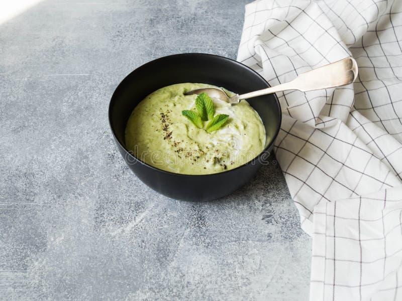 I piselli scremano la minestra del purè in ciotola nera Minestra crema verde vegetariana dei piselli con la menta in ciotola su f fotografie stock