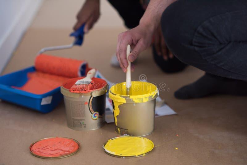I pittori coppia preparano il colore per dipingere fotografie stock