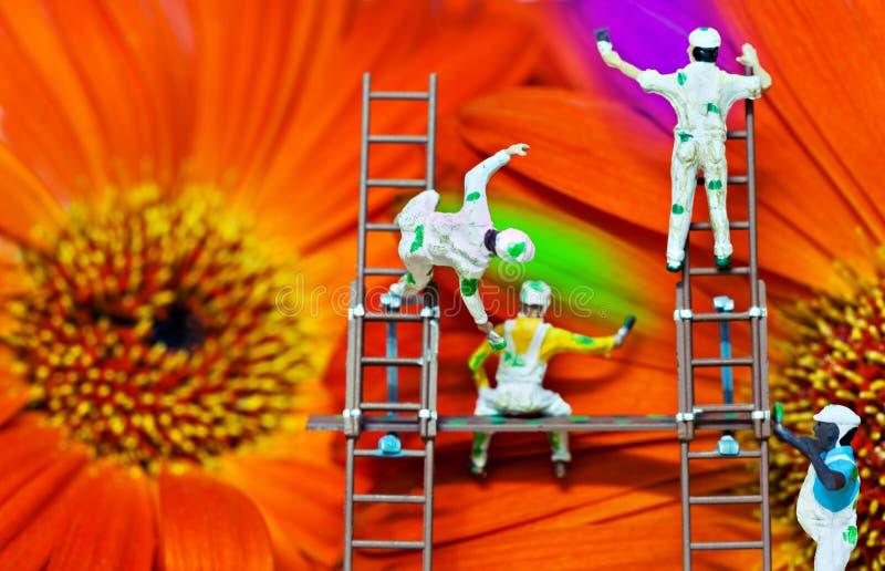 I pittori della natura, piccola gente, dipingente fiorisce fotografie stock