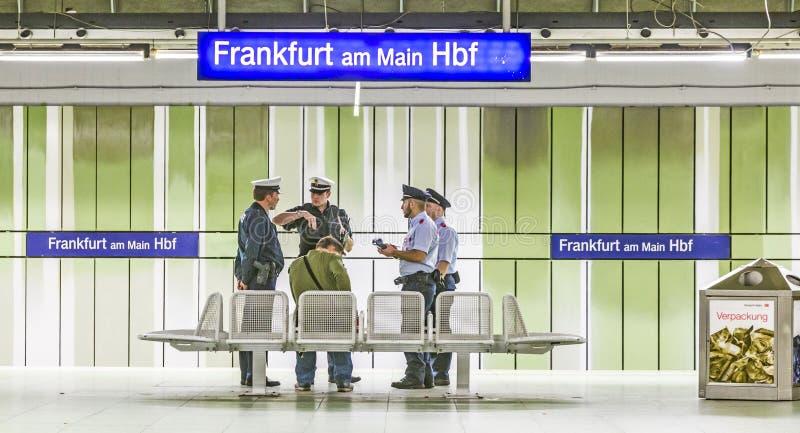 I poliziotti ferroviari controllano un passeggero per vedere se c'è un biglietto valido alla stazione principale di Francoforte fotografia stock