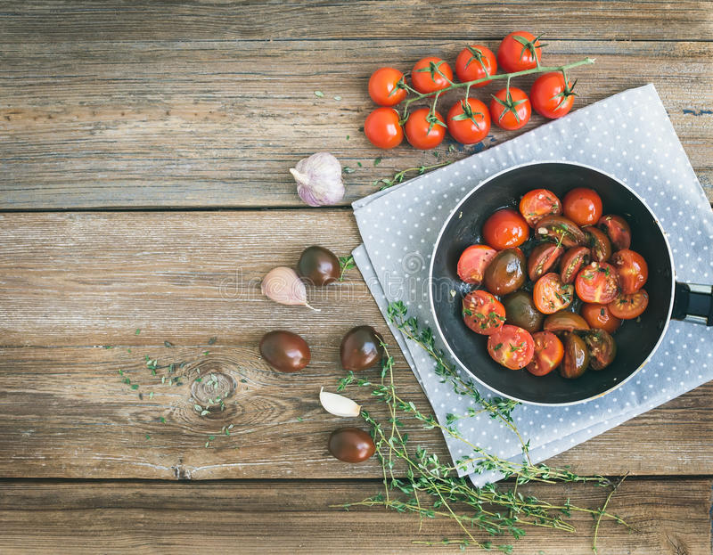 I pomodori ciliegia arrostiti con aglio e timo in una cottura filtrano la o fotografia stock libera da diritti