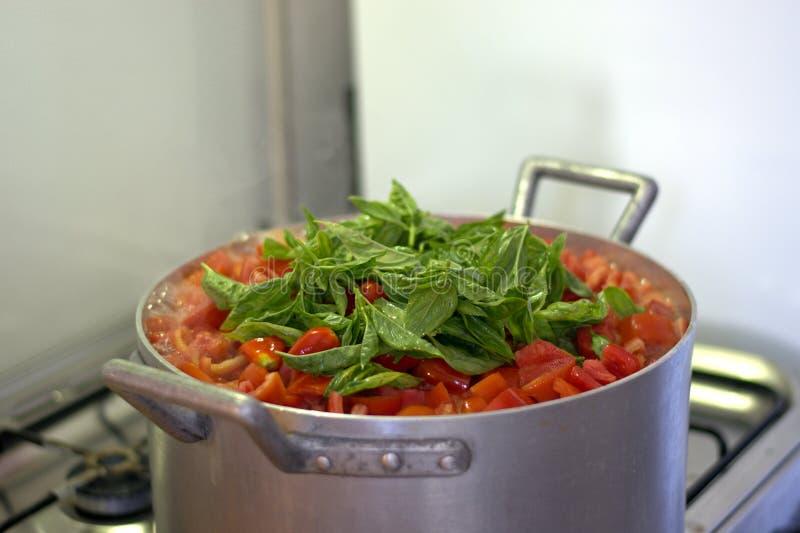 I pomodori hanno tagliato, pronto ad essere cucinato in vaso con basilico fotografie stock libere da diritti