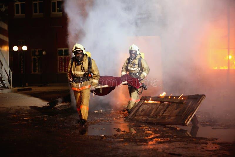 i pompieri di incidente salvano la vittima immagine stock