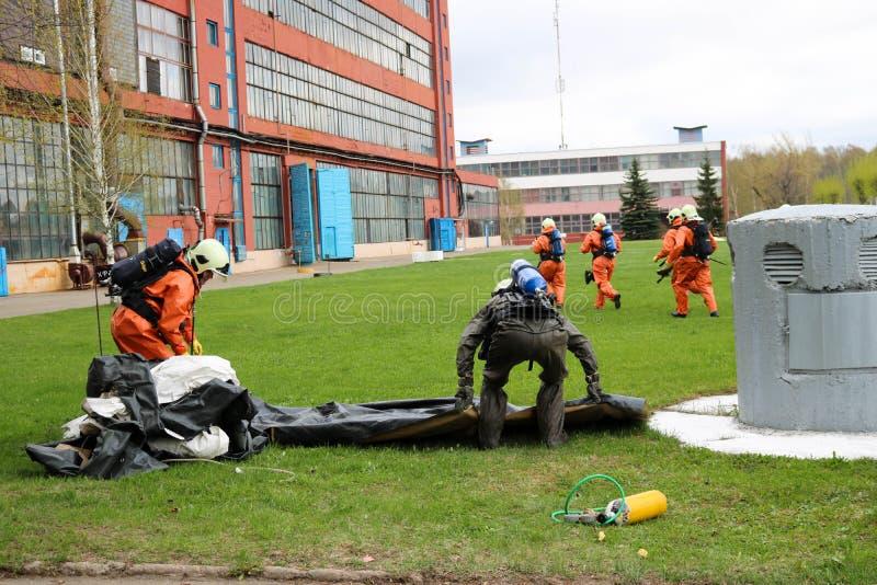 I pompieri professionisti, i soccorritori in vestiti a prova di fuoco protettivi, i caschi bianchi e le maschere antigas stanno p fotografia stock
