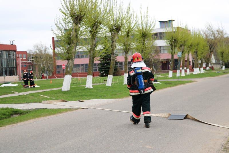 I pompieri professionisti, i soccorritori in vestiti a prova di fuoco protettivi, i caschi e le maschere antigas con le bombole d fotografia stock