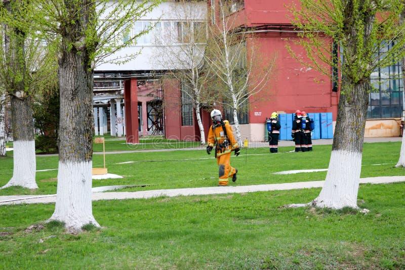 I pompieri professionisti, i soccorritori in vestiti a prova di fuoco protettivi, i caschi e le maschere antigas con le bombole d immagine stock libera da diritti