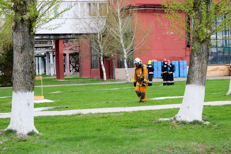 I pompieri professionisti, i soccorritori in vestiti a prova di fuoco protettivi, i caschi e le maschere antigas con le bombole d immagini stock libere da diritti