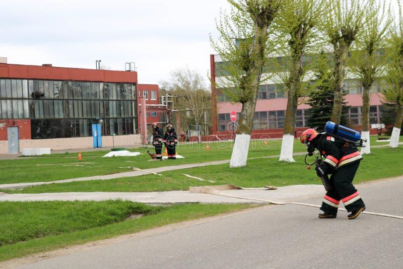 I pompieri professionisti, i soccorritori in vestiti a prova di fuoco protettivi, i caschi e le maschere antigas con le bombole d fotografie stock libere da diritti