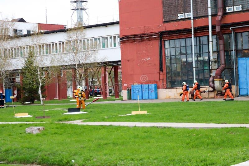 I pompieri professionisti, i soccorritori in vestiti a prova di fuoco protettivi, i caschi e le maschere antigas con le bombole d immagini stock