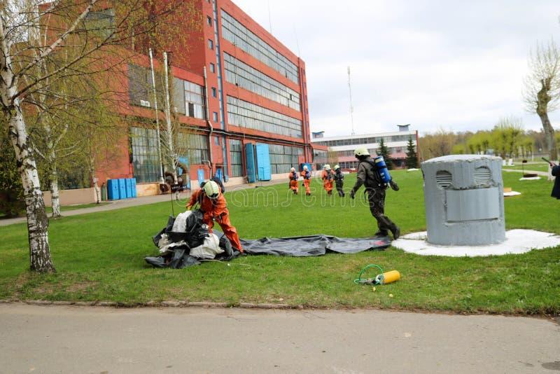 I pompieri professionisti, i soccorritori in vestiti a prova di fuoco protettivi, i caschi e le maschere antigas fuggono la gente fotografia stock libera da diritti