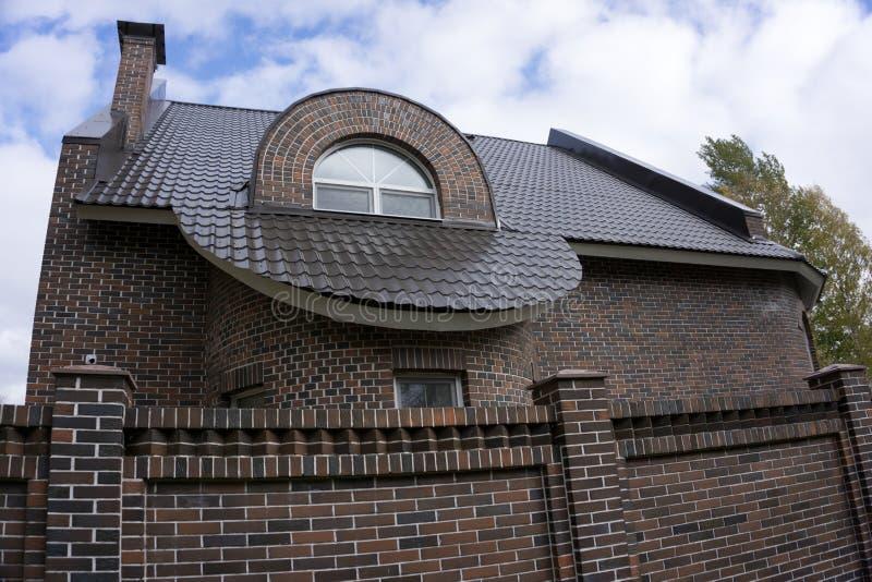 I portoni neri dell'entrata della strada privata del metallo hanno messo in recinto del mattone con la grande casa nel fondo fotografia stock