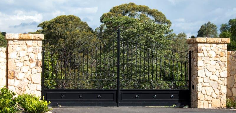 I portoni rurali dell'entrata della proprietà della strada privata del metallo hanno messo in recinto del mattone dell'arenaria c fotografia stock libera da diritti
