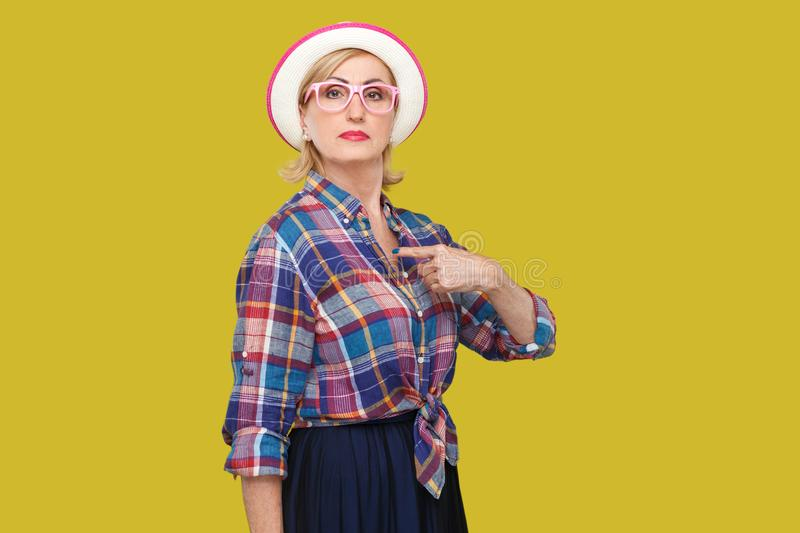 Because I am. Portrait of proud serious modern stylish mature woman in casual style with hat and eyeglasses standing, pointing. Herself and looking at camera stock photos