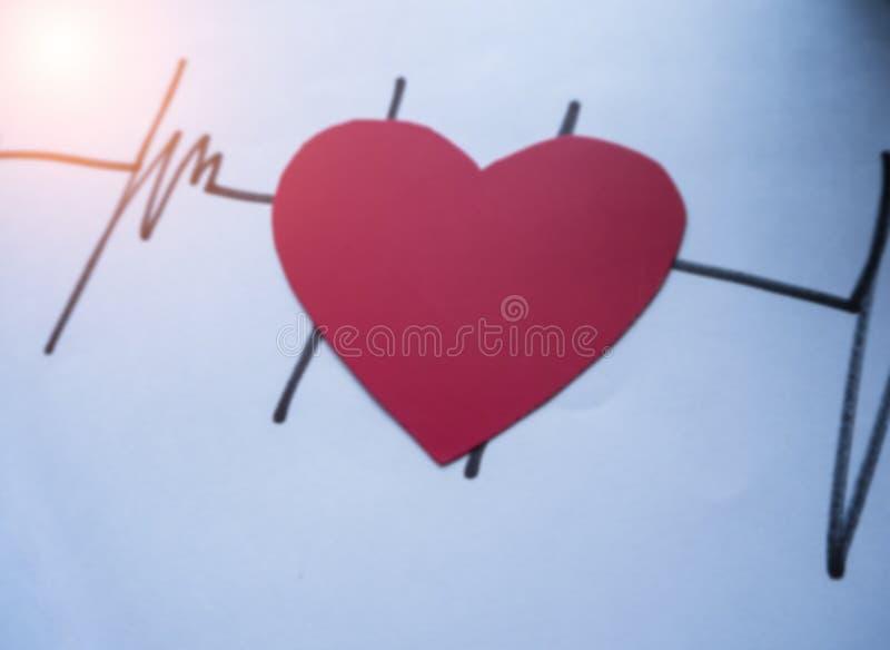 I precedenti leggeri confusi di progettazione della carta rossa cutted del cuore messa sul disegno di frequenza cardiaca fotografia stock