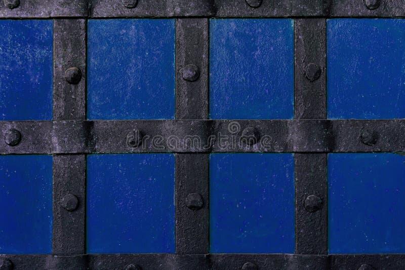 I precedenti sono dipinti con pittura blu con i fasci ed i ribattini del metallo fotografia stock libera da diritti