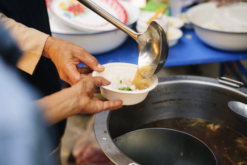 I problemi di fame del povero sono stati alimento donato per ridurre la fame: il concetto di penuria alimentare nel mondo: Doni l immagini stock