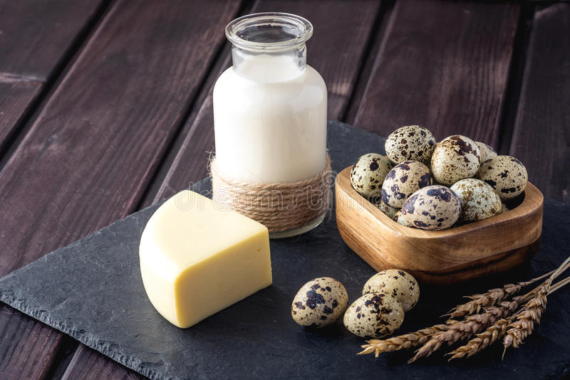 I prodotti di fattoria di Eco mungono, formaggio, il yogurt, uova su fondo di legno scuro Il concetto della casa ha prodotto l'al fotografia stock