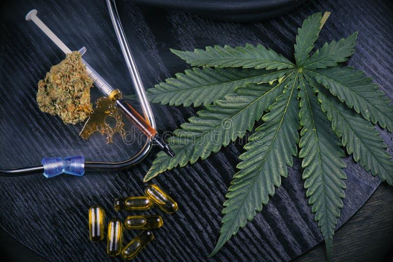 I prodotti medici della marijuana con le cannabis coprono di foglie sul nero fotografia stock libera da diritti