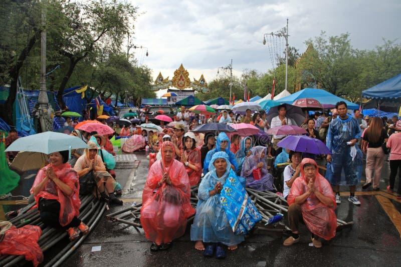 I protestatari tailandesi pregano durante la pioggia il giorno di Visakha Bucha fotografia stock libera da diritti