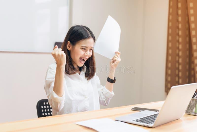 I pugni delle donne di affari che sono emozionanti di successo hanno espresso la gioia perché funzionano per raggiungere i suoi s fotografie stock libere da diritti
