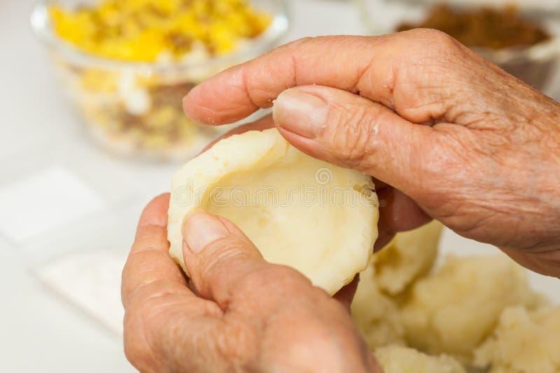 I punti della preparazione del piatto colombiano tradizionale hanno chiamato le patate farcite fotografie stock libere da diritti