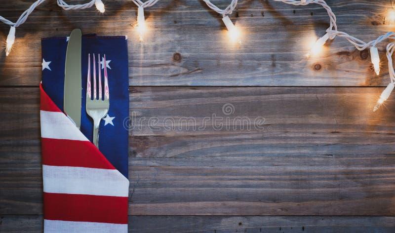 i quarti della Tabella di cena del BBQ della celebrazione di luglio dispongono la regolazione con le luci sul fondo di legno rust immagine stock libera da diritti